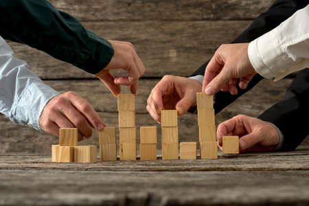 business relationship: Hands of five businessman holding wooden blocks placing them into a structure. Conceptual of teamwork, strategy and business start up.