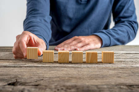 placing: Front view of a man placing six blank wooden cubes in a row on a textured rustic wooden desk.