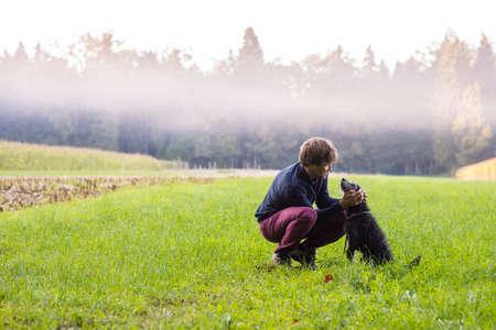 amigos abrazandose: Hombre joven que se agacha para acariciar a su perro negro en un hermoso prado verde con niebla blanca por encima de ellos y el bosque en el fondo. Foto de archivo