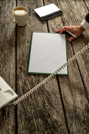 telephone cord: High angle closeup view of male hand holding a pen leaning on wooden office desk with blank sheet of paper, digital tablet and cup of cappuccino wit telephone cord going across the image.