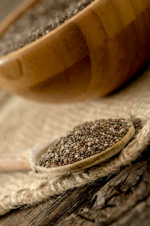 sac: Closeup of wooden spoon full of healthy organic chia seeds with wooden bowl in background lying on burlap sac.