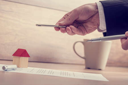 key handover: Closeup of male hands holding a house key and a pen over a contract of house sale lying on wooden desk with house miniature and coffee cup in background. Stock Photo