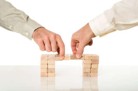 Konzeptionelle Image von Unternehmen Fusionen und Zusammenarbeit - zwei männliche Hände Beitritt Bemühungen um eine Brücke von Holzpflöcken auf einem weißen Schreibtisch mit Reflexion über weißem Hintergrund zu bauen.