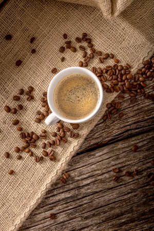 burlap sac: Top view of still life with a cup of freshly prepared cup of aromatic black coffee and coffee beans scattered around over burlap sac covering a textured wooden desk. Stock Photo