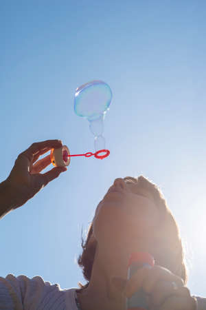 carelessness: Closeup of young woman blowing soap bubbles under clear blue sky. Stock Photo