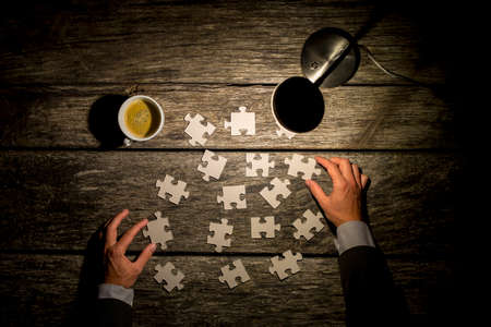 business puzzle: Top view of male hands in elegant business suit trying to find a solution to a problem by arranging and matching puzzle pieces on a textured rustic wooden desk wit a lit table lamp and cup of coffee.