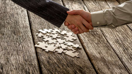 strategizing: Closeup of male and female business partners shaking hands over a pile of puzzle pieces lying on a textured rustic wooden desk. Conceptual of teamwork and strategy planning.