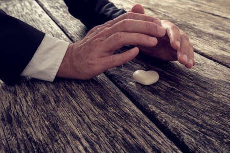 sheltering: Closeup view of male hands in elegant suit making protective sheltering gesture over a marble made heart lying on textured wooden planks, with retro filter effect. Stock Photo