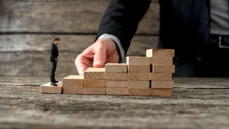 Geschäftsmann Bau einer Treppe aus Holzpflöcken für einen anderen Unternehmer die Leiter des Erfolgs zu erklimmen.