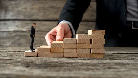 Businessman building a staircase of wooden pegs for another entrepreneur to climb up the ladder of success. Stockfoto
