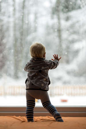 looking up: Toddler boy standing up against a window looking out to observe a snowy nature and forest. Stock Photo