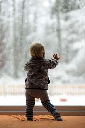 Toddler jongen opstaan tegen een raam met uitzicht op een besneeuwde natuur en bos te observeren. Stockfoto