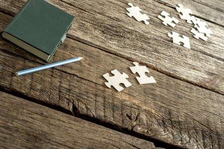 piezas de rompecabezas: cojín de nota verde, lápiz y las piezas del rompecabezas dispersos se extiende sobre un escritorio de madera con textura. Conceptual de la educación, la investigación y la resolución de problemas.