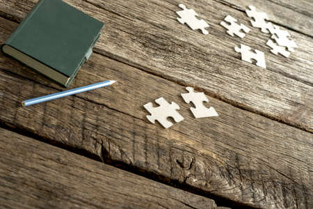 puzzle pieces: Green note pad, pencil and scattered puzzle pieces lying on a textured wooden desk. Conceptual of education, research and problem solving. Stock Photo