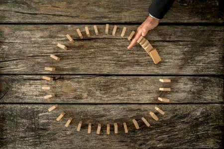 solucion de problemas: El hombre de negocios se interrumpe el cayendo dominos colocados en un círculo con su mano. Conceptual de la crisis y la gestión de problemas. Foto de archivo