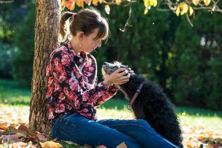 amigos abrazandose: Mujer joven que se sienta bajo un árbol del otoño que abraza a su perro negro al aire libre en un parque. Foto de archivo