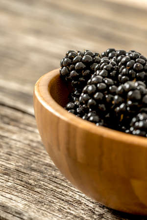 heaping: Closeup of delicious ripe blackberries heaping in a wooden bowl placed on rustic textured oak desk.