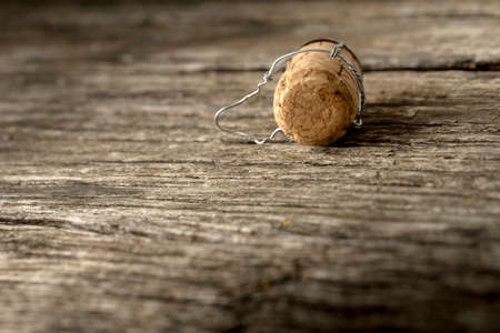 message board: Champagne cork lying on a rustic textured wooden board, with copy space.