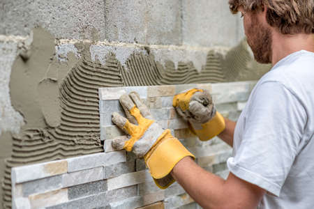 diy: Man pressing an ornamental tile into a glue on a wall with gloved hands in a DIY concept.
