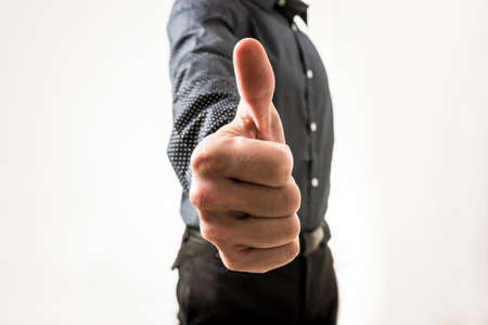 Closeup of businessman showing a thumbs up sign towards you. Over white background. Archivio Fotografico