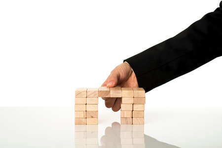 metaphoric: Hand of a businessman assembling a bridge of wooden pegs on white desk with reflection. Conceptual of problem solving. Stock Photo