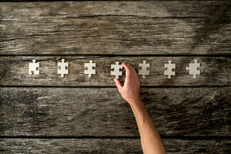 compatibility: Top view of male hand placing seven blank puzzle pieces in a row on textured wooden boards. Stock Photo