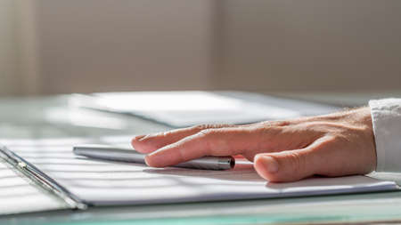 finalized: Male hand lying on a contract or document and a pen. Conceptual of closed deal and business success. Stock Photo