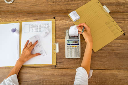 calculations: Top view of female accountant making calculations using adding machine with folders, documents and receipts on her office workdesk.