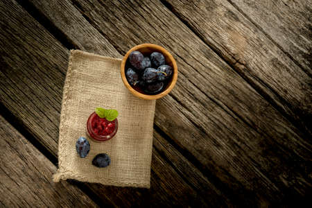 burlap sac: Top view of burlap sac lying over rustic textured wooden desk with glass jar full of jam, ripe plums and bowl of juicy plums on it.