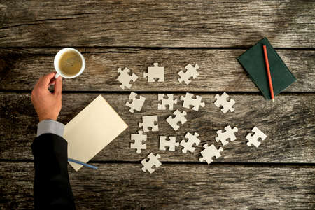 hand with pencil: Businessman reaching for a cup of coffee on his rustic wooden desk as he searches for solution to a problem  with puzzle pieces scattered on his desk next to a blank paper and notepad with a pen.