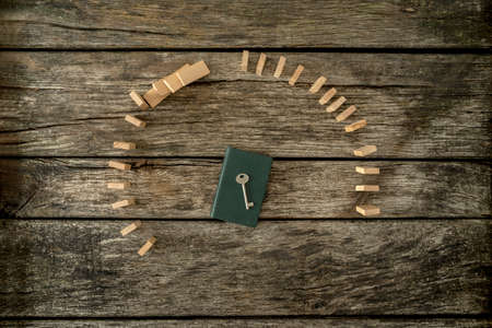 err: Top view of key lying on closed notebook surrounded by two curves of dominoes - one falling and one standing firm.