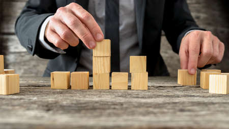 Concept of business strategy and planning - front view of male hand placing and positioning wooden blocks in various structures.