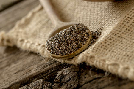 burlap sac: Wooden spoon full of healthy chia seeds lying on a linen textile. Stock Photo