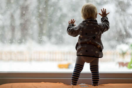 looking at: View form behind of toddler child standing in front of a big window leaning against it looking outside at a snowy nature.