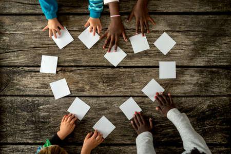 질감 된 소박한 나무 보드 위에 흰색 카드의 심장 모양을 조립하는 혼합 된 인종의 4 명의 자녀의 상위 뷰. 스톡 콘텐츠