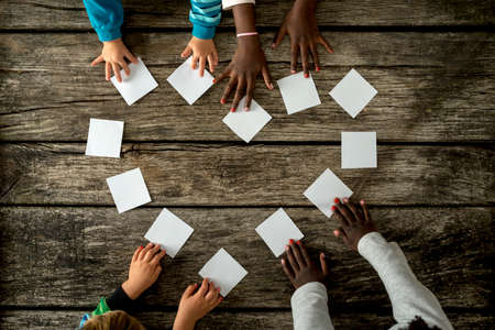 Top view of four children of mixed races assembling a heart shape of white cards over a textured rustic wooden boards.