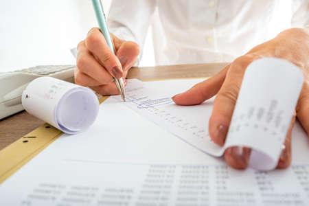 Primer plano de contable de sexo femenino que mira a través de los recibos mientras se trabaja en un informe.