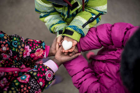 Top view of three toddler girls in winter jackets holding their hands joined together with the hand on top holding a heart made of marble.