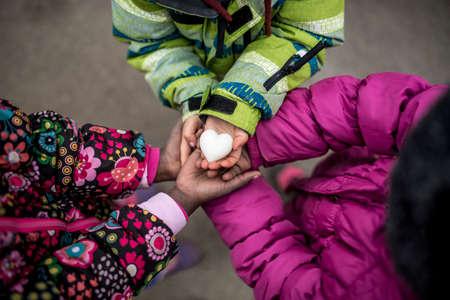 manos unidas: Vista superior de tres niñas pequeñas en las chaquetas de invierno que sostiene sus manos se unió junto con la mano sobre la celebración de un corazón hecho de mármol.
