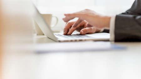 tabla de surf: Detalle de las manos del hombre de negocios usando la computadora portátil con una de las manos borrosas.
