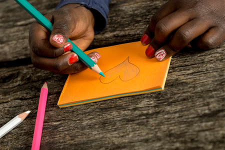 colour pencil: Closeup view of an African-American girl with red painted nails colouring a heart shape with blue colour pencil drawn on orange post it paper.