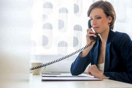 landline phone: Young elegant businesswoman sitting at her office desk making a telephone call using white landline phone with paperwork or document in a folder in front of her.