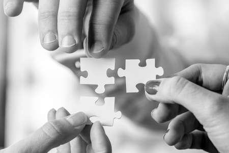 Image en noir et blanc de trois personnes, homme et femme, tenant des pièces du puzzle pour les assortir. Conceptuel du travail d'équipe, de la coopération et de la résolution de problèmes. Banque d'images