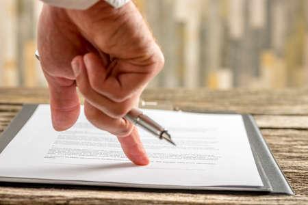 Primer de la mano masculina que sostiene una pluma que señala a una línea al final de un contrato, documento o formulario de solicitud listo para la firma. Foto de archivo