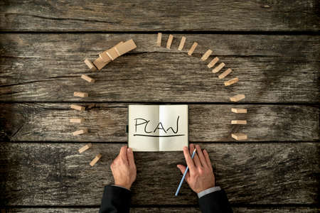 the view option: Top view of businessman planning the future - open notebook with word Plan on his desk surrounded by two curves of dominos, one standing and the other falling.
