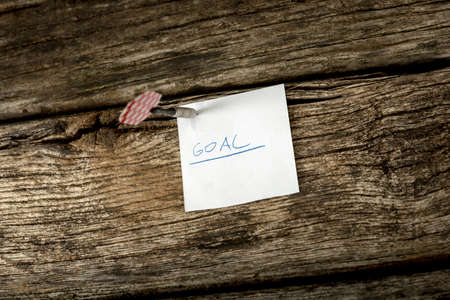 setting goals: White piece of paper with the word Goal pinned to a rustic wooden boards with a dart. Conceptual of setting goals and aspirations for the near future.