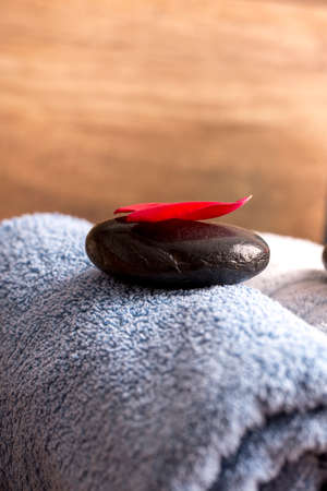 background settings: Closeup of red rose petal lying on black zen stone on top of blue rolled towel.