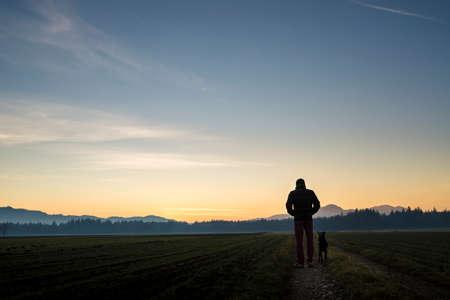 Ansicht von hinten von einem Mann mit seinem schwarzen Hund in der Dämmerung auf einer Landstraße in der Ferne und schönen Abendhimmel über führen durch schöne Landschaft von Feldern mit Wald spazieren.