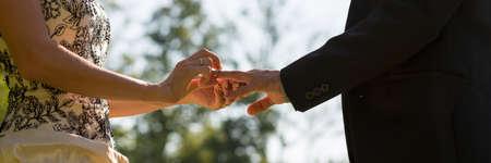 heirat: Hochzeitszeremonie - Nahaufnahme Ansicht der Braut in der goldenen Hochzeit Kleid, das einen Ring an ihrem Gatten Finger draußen in der Natur setzen. Lizenzfreie Bilder