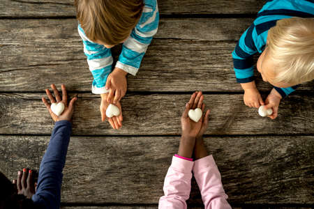 black kid: Top view of four children of mixed races each holding a marble heart in hands. Conceptual of equality and friendship.